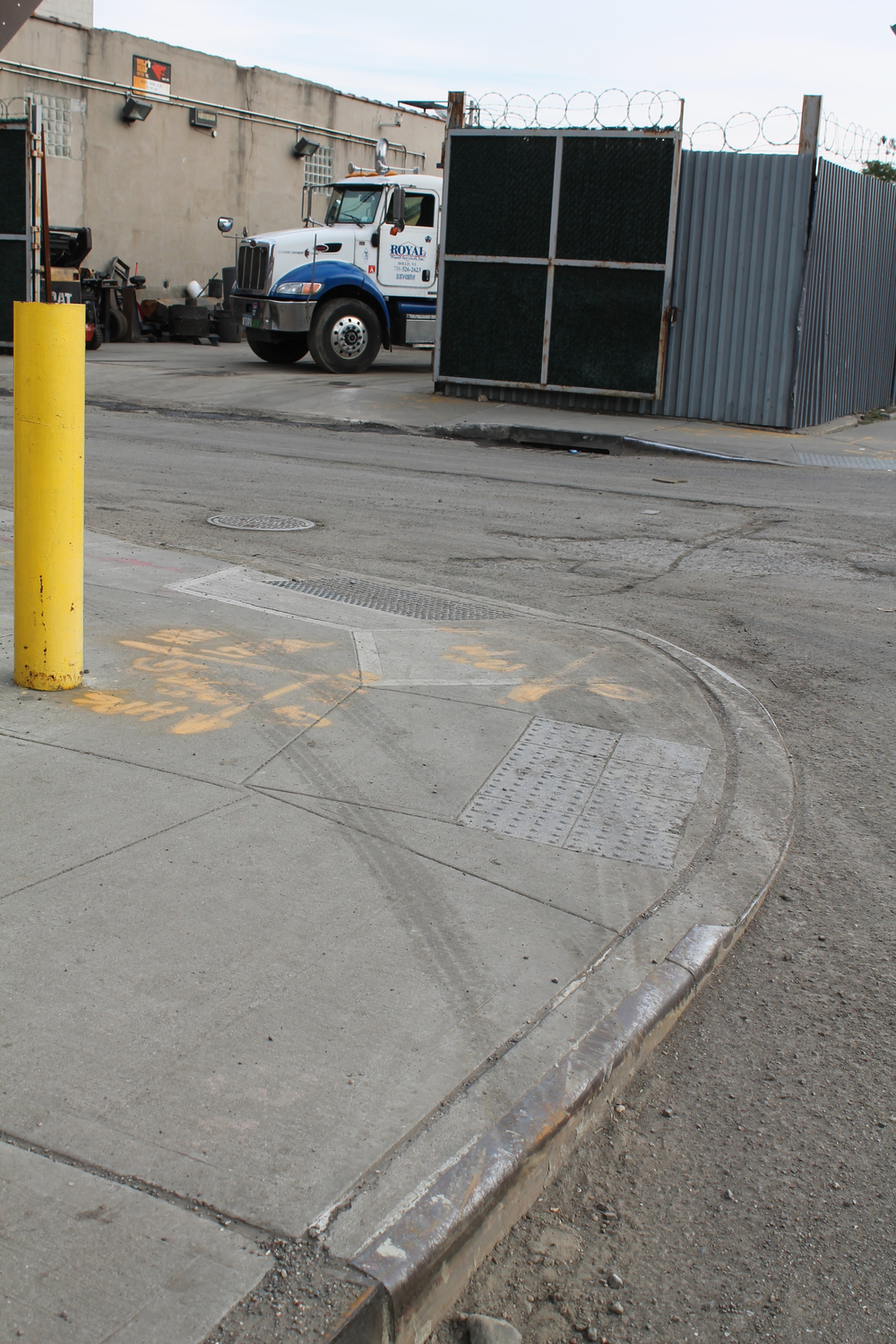 Some large and heavy commercial trucks can only make wide right turns onto 170th Street in Jamaica, Queens, by jumping their wheels onto the sidewalk, making use of sidewalks potentially dangerous.  These tire tracks were photographed on October 28, 2014.  Source :  Louis Flores