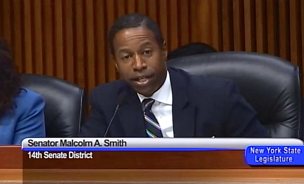 Former New York State Senator  Malcolm Smith  (D-Queens) at a healthcare hearing on February 3, 2014, faces a second trial over federal criminal corruption charges after a first court case ended last June in a mistrial.  Source :  New York State Senate/YouTube Screen Shot