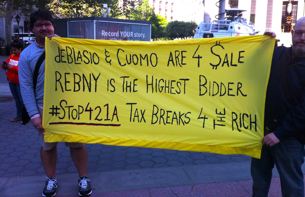 Two activists, who were not affiliated with any nonprofit groups, attended the #1MillionHomes rally in Foley Square, holding up a protest banner with politically-direct messaging, questioning the role of real estate campaign contributions on the official policies of Mayor Bill de Blasio and Governor Andrew Cuomo.  At left is Louis Flores, the author of this article and the publisher of Progress Queens.  Source :  Progress Queens
