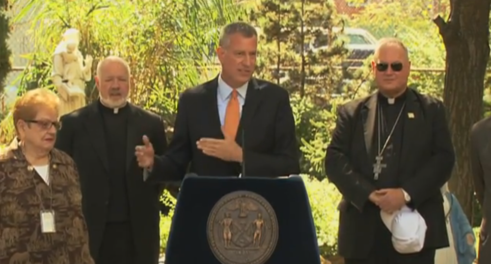 Mayor  Bill de Blasio , center, with  Cardinal Timothy Dolan , right, at a press conference announcing an initiative to provide new, incremental emergency housing for the homeless.  Source :  New York City Mayor's Office/YouTube (Public Domain)