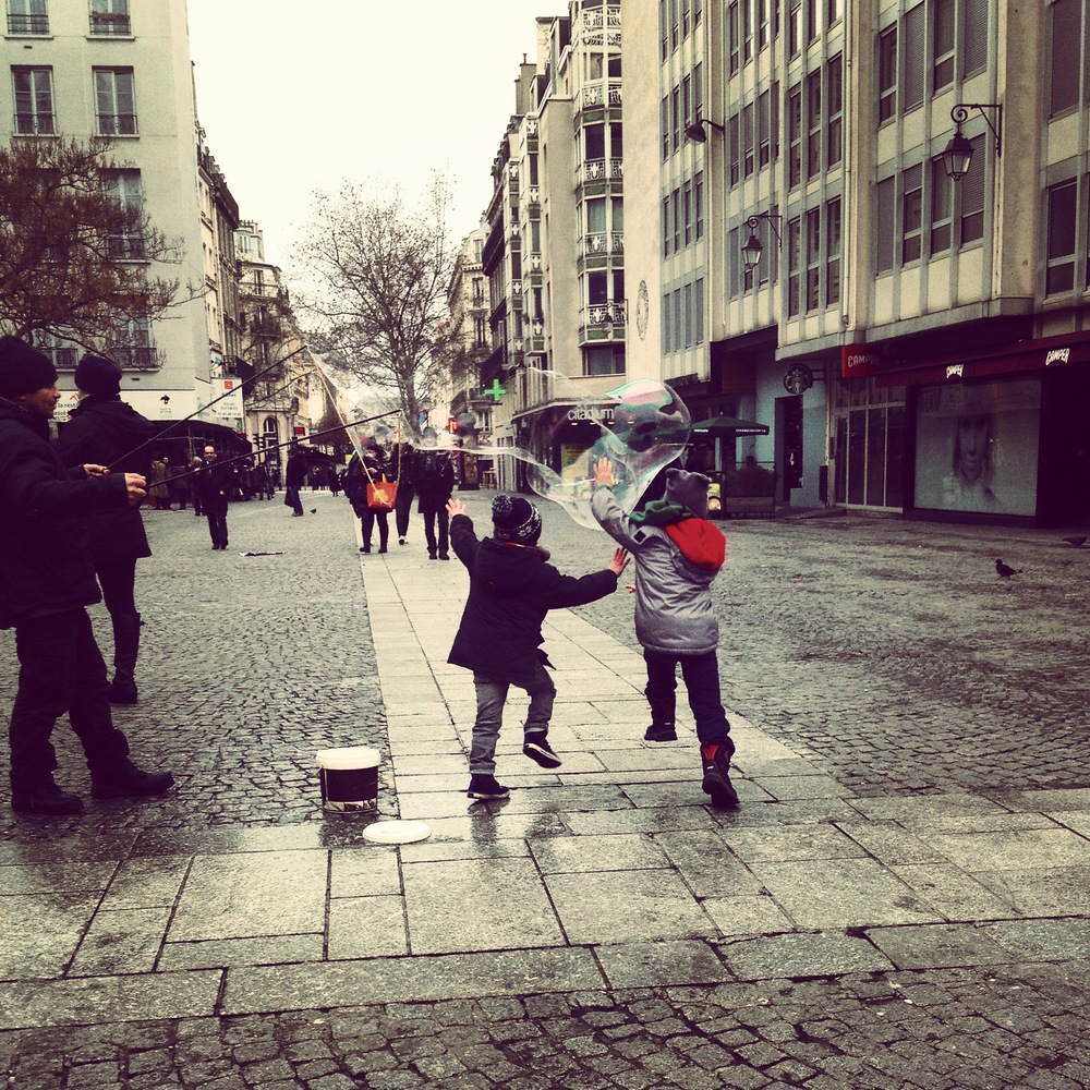 My son and a new-found friend, chasing giant bubbles outside the Pompidou Center.