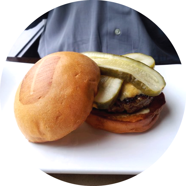 WELSH RABBIT BURGER- ANAHEIM signature blend of beef patty, smothered in broiled vintage English cheddar cheese sauce, with bread & butter pickles