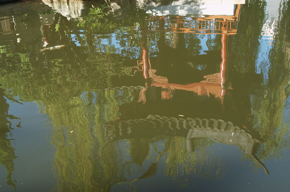 The reflection of a pagoda structure in a pond in the garden