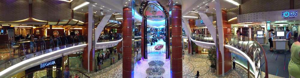 A panorama of the Royal Promenade from the staircase. Guest services on the left and the photo shop on the right.