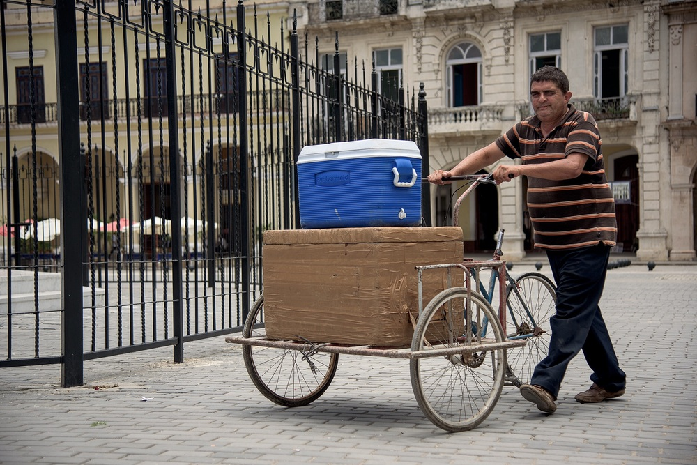 A man makes deliveries for work, and sells water to tourists from a blue cooler, likely it came into Cuba with relatives on charters from Miami.  We saw everything from bike tires to hula hoops and baby strollers on the baggage claim in Havana on our Miami charter.