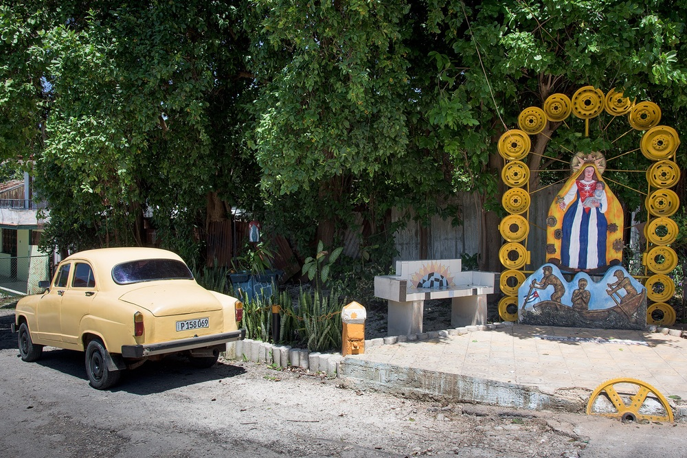 "Another old Soviet era car sits near ""Our Lady of Guadelope"" art work created from old tire rims at the Muraleando Project."