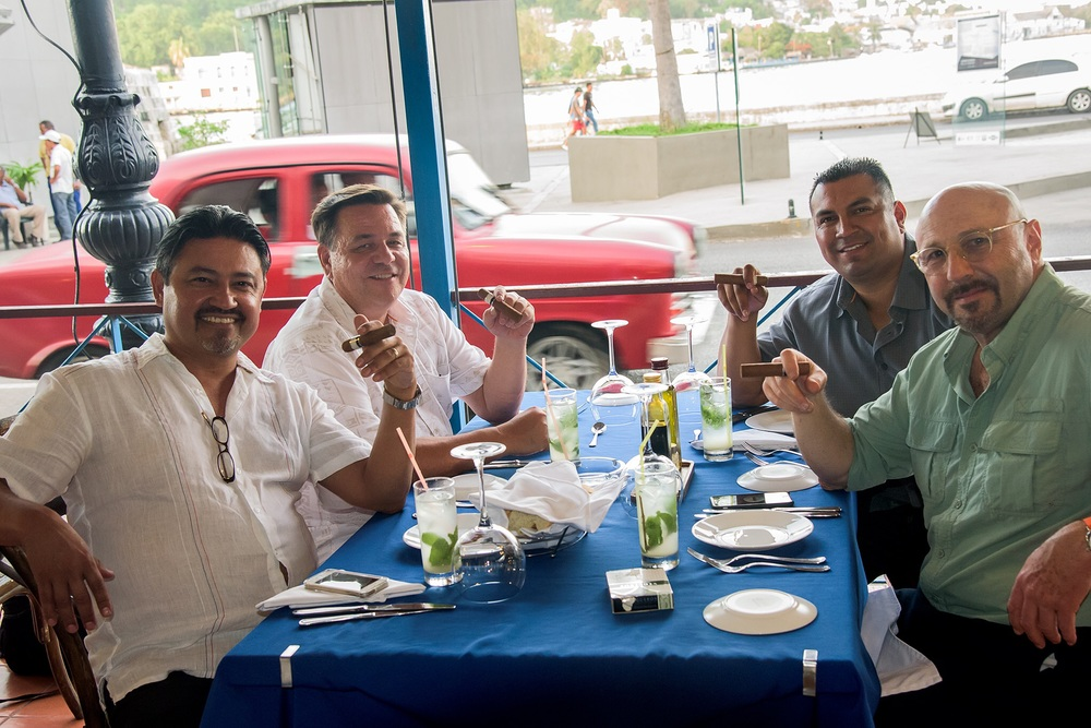 A group of gentlemen from California enjoy cigars after a meal at a state run tourist restaurant
