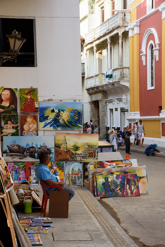 A slice of life in the old town: an art dealer sits with his wares while tourists take photos  and workers make repairs.
