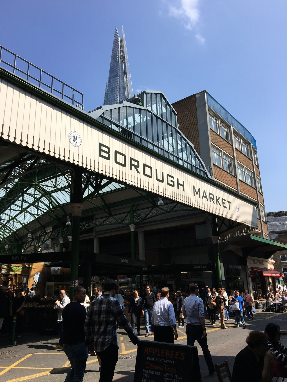 "A large covered food market in the Southwark Area, sits under another modern building known as the ""Shard"""