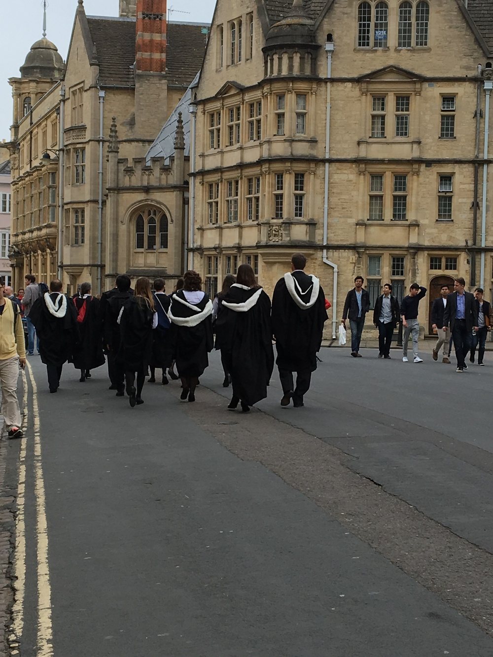 A group of students led by their faculty member make their way in full regalia on foot to their graduation ceremony.