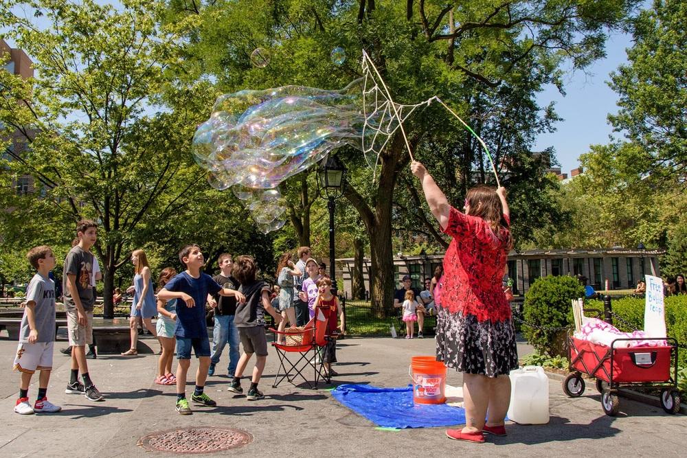 A busker creates bubbles for children to play with in Washington Square Park