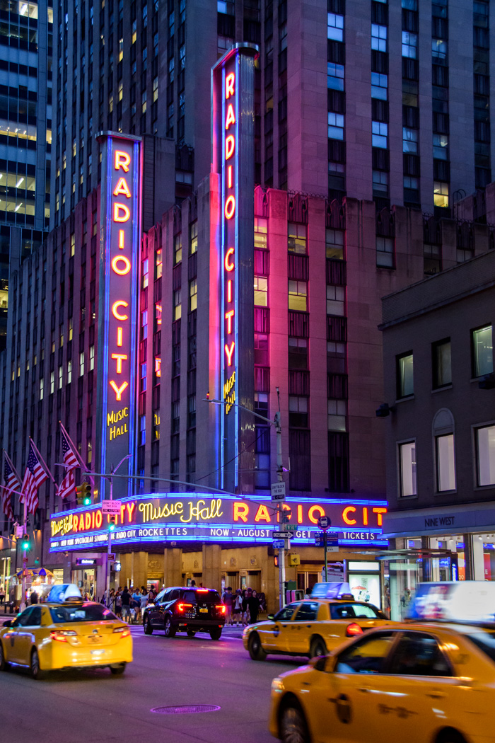 Radio City Music Hall and iconic yellow cabs in NYC