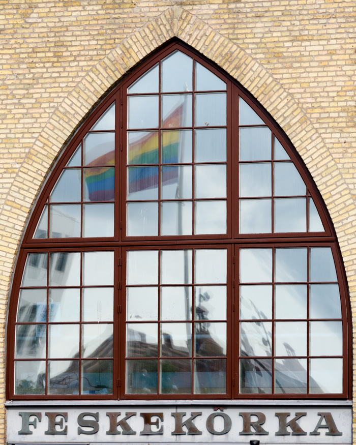 A window of the Feskekorka reflects a nearby pride flag on pride weekend.