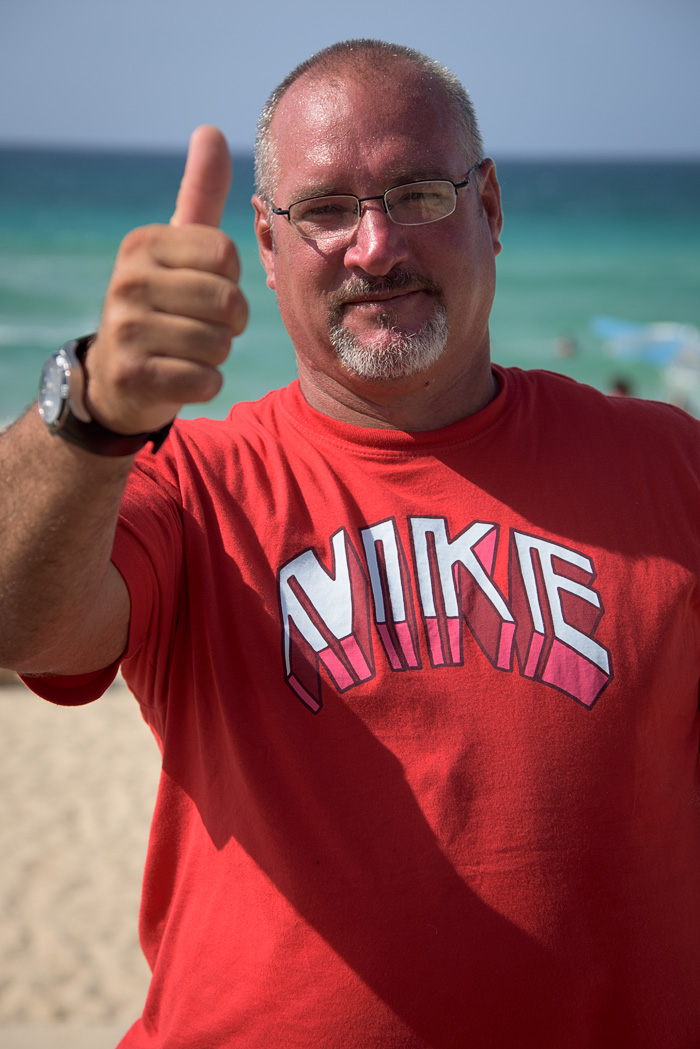 A man on the beach expresses his enthusiasm for Americans with his shirt and his gestures!