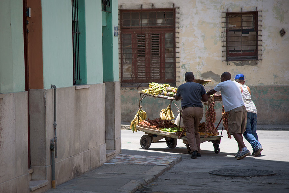 Three men struggle to maneuver a fruit cart in the streets.
