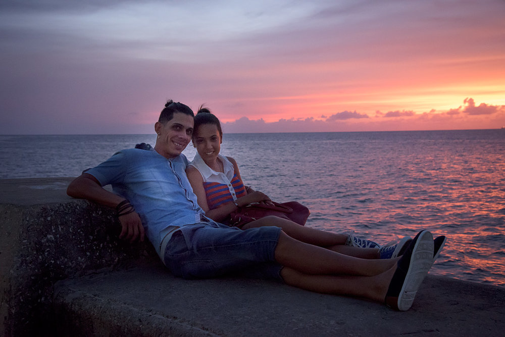 A young couple enjoys the sunset on the malecon in Havana
