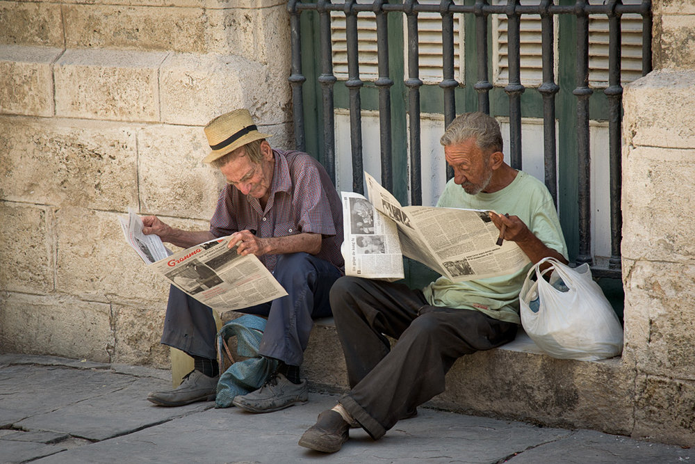 Two gentlemen read the news on the stoop on the outskirts of Old Havana