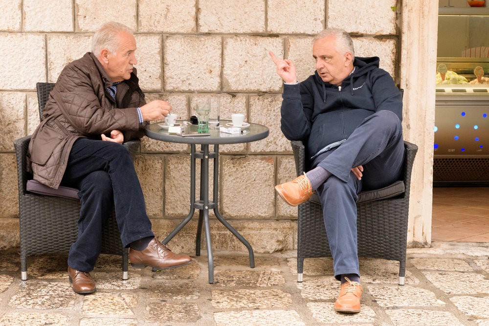 Inside the walled village, there are many cafes and shops, two gentlemen enjoy a coffee on a cloudy Saturday morning.