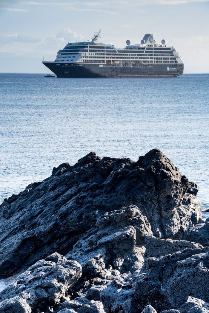 Azamara Quest at anchor near the lava rock coast of Sicily.