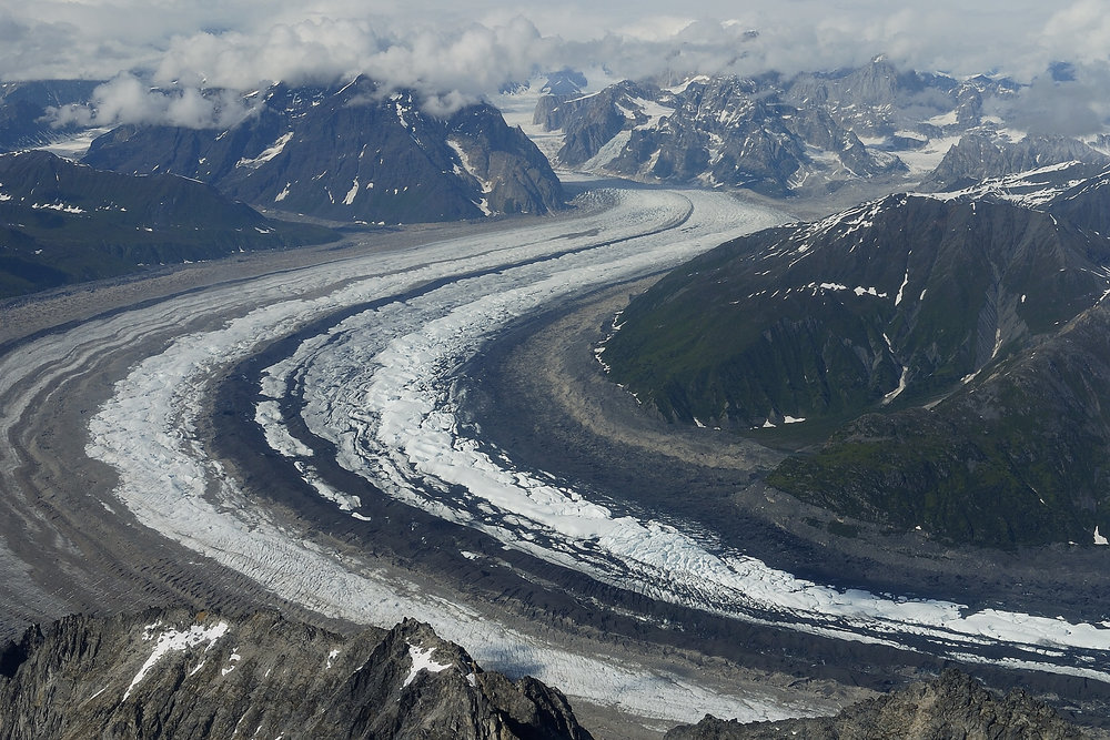 From the air, the Ruth Glacier appears as a river of ice flowing through the landscape. For more on Alaska  see our Alaska Trip Report here