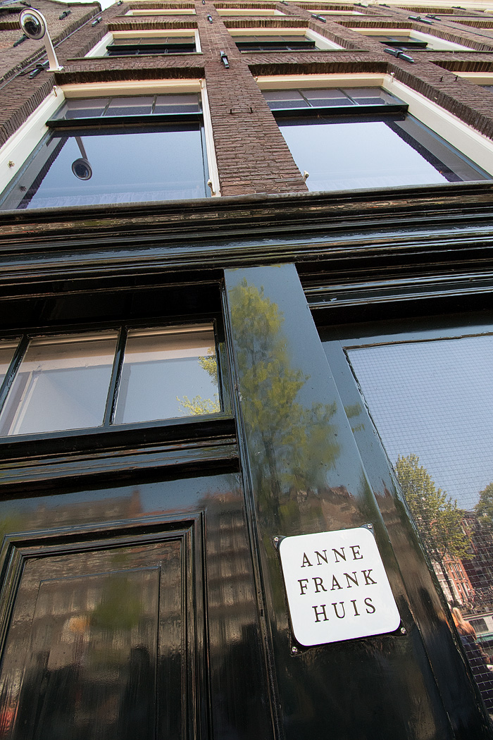 The Prinsengracht canal is reflected on the building that housed Anne Frank and her family during Nazi occupation.