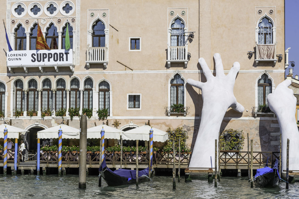 "Lorenzo Quinn's art installation was meant to draw attention to the ""support"" Venice needs as tourism and climate changes affect the coastal city."