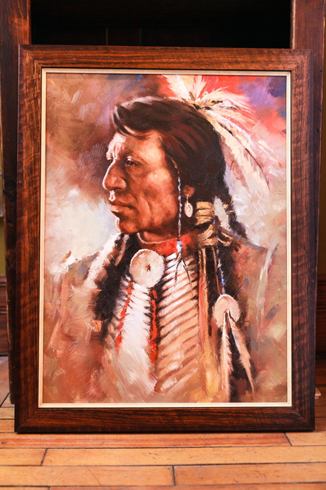 Native American warrior framed in tooled wooden frame with cream fillet.