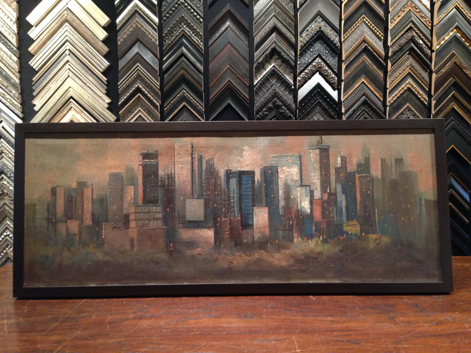 Mid-Century skyline painting framed in dark wood.