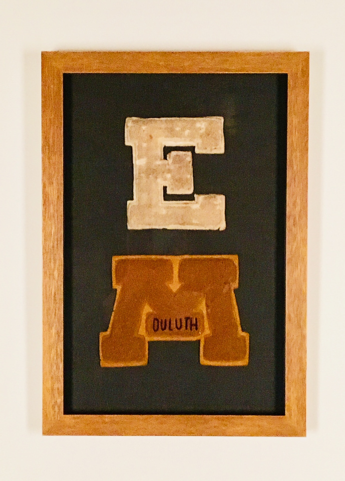 Varsity letters sewn to charcoal linen and shadowboxed in ochre frame.