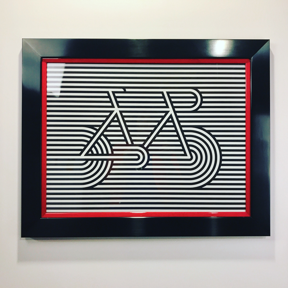 Artcrank print framed in a glossy black frame stacked with red.