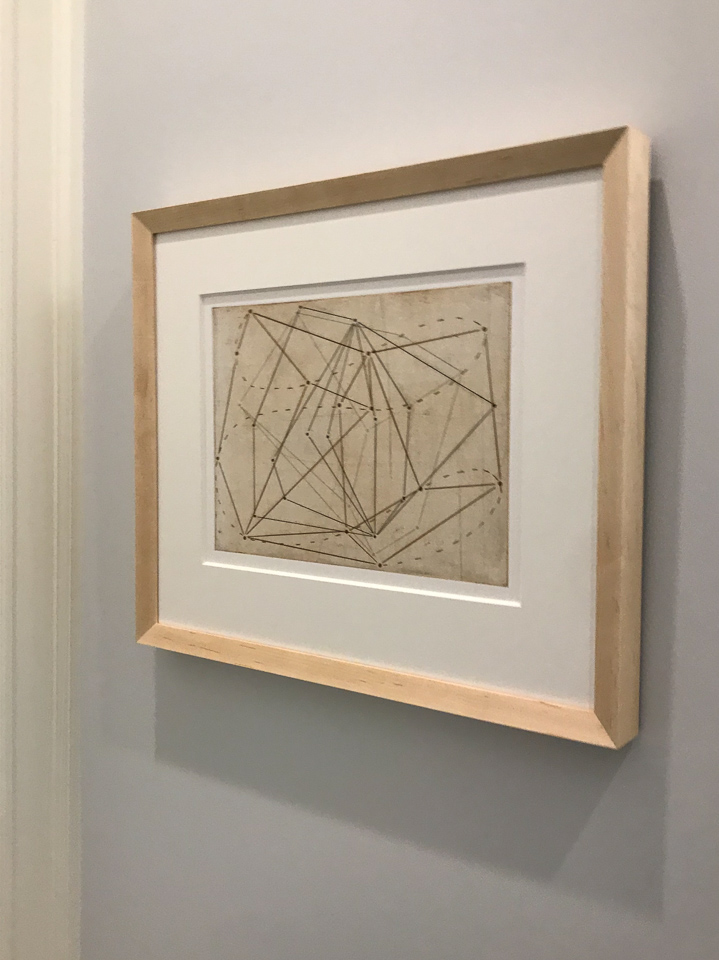 Beautiful geometric print framed in angled maple.