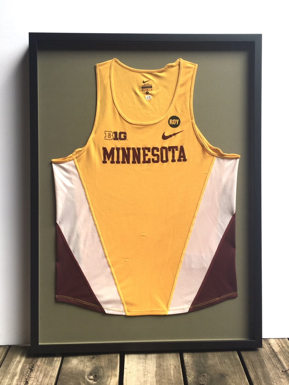 University of Minnesota track jersey shadowboxed in black.