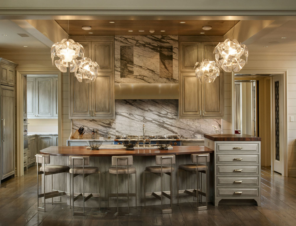 The modern pendant drop lanterns light the way to a spacious pantry with additional ovens, storage, and refrigerators.
