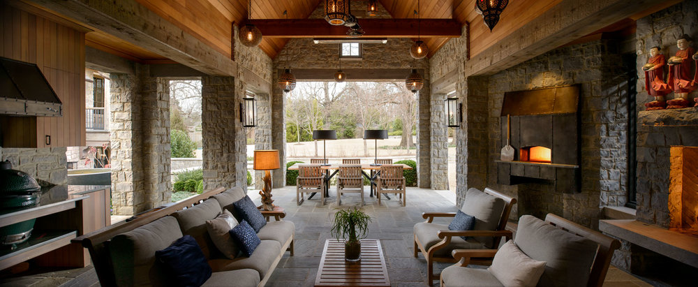 The veranda features several amenities worthy of a grand backyard party, including a wood-burning fireplace, stone pizza oven, and outdoor kitchen area with a Big Green Egg.