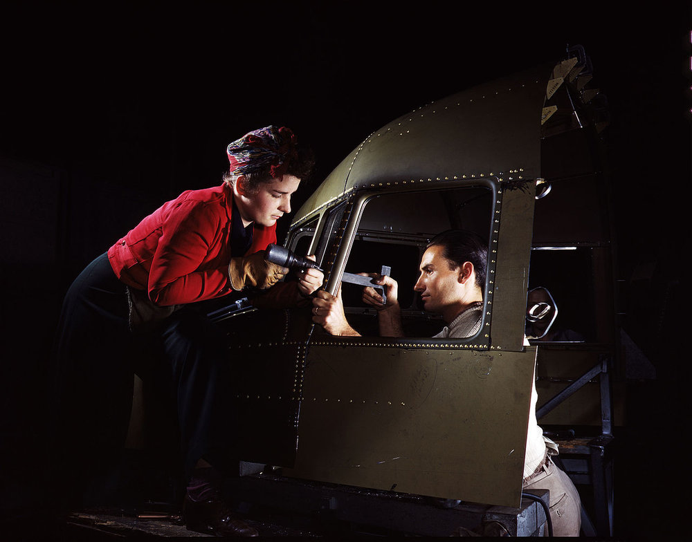 A man and woman riveting team working on the cockpit shell of a C-47 aircraft at the plant of North American Aviation (1942). Photographer: Alfred T. Palmer