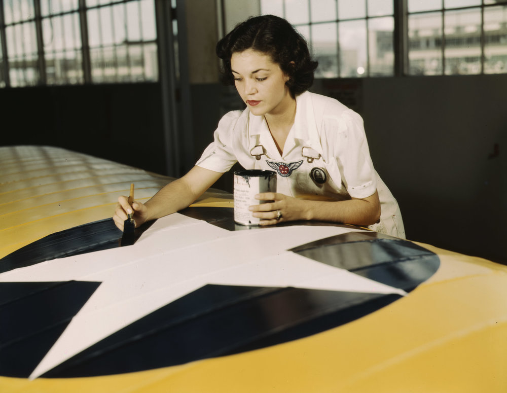 Mrs Irma Lee McElroy painting the American insignia on airplane wings at Naval Airbase, Corpus Christi, Texas. Photographer: Howard R. Hollem