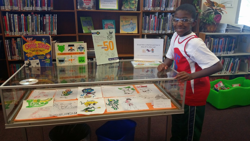 Chigozie next to his artwork. The 11 year old recentlyhad a display at the White Oak Branch of the Silver Spring Library.