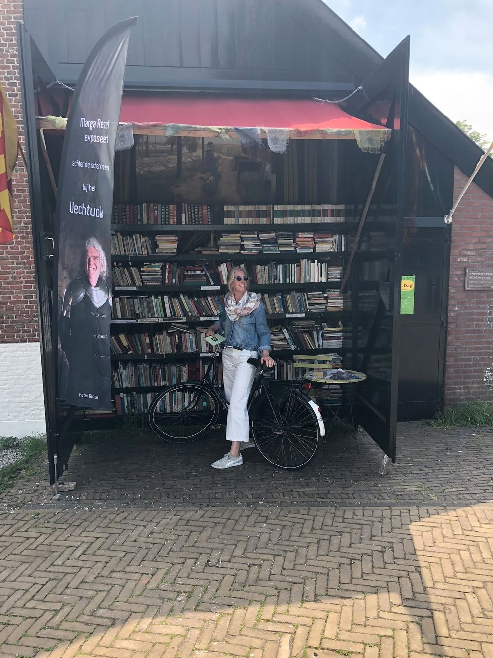"Anne, enjoying a day off biking in Amsterdam. This bookstore sold its wares on the ""honor system,"" asking patrons to choose their books and leave their money without a shopkeeper to oversee it."