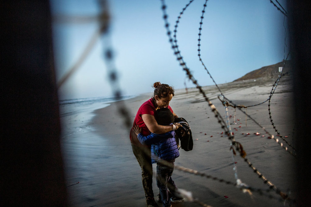 A  Central American migrant hugging her child on the beach in San Diego  after crossing the border wall at Tijuana Beach, Mexico. December 2018. Credit: Fabio Bucciarelli for Yahoo News