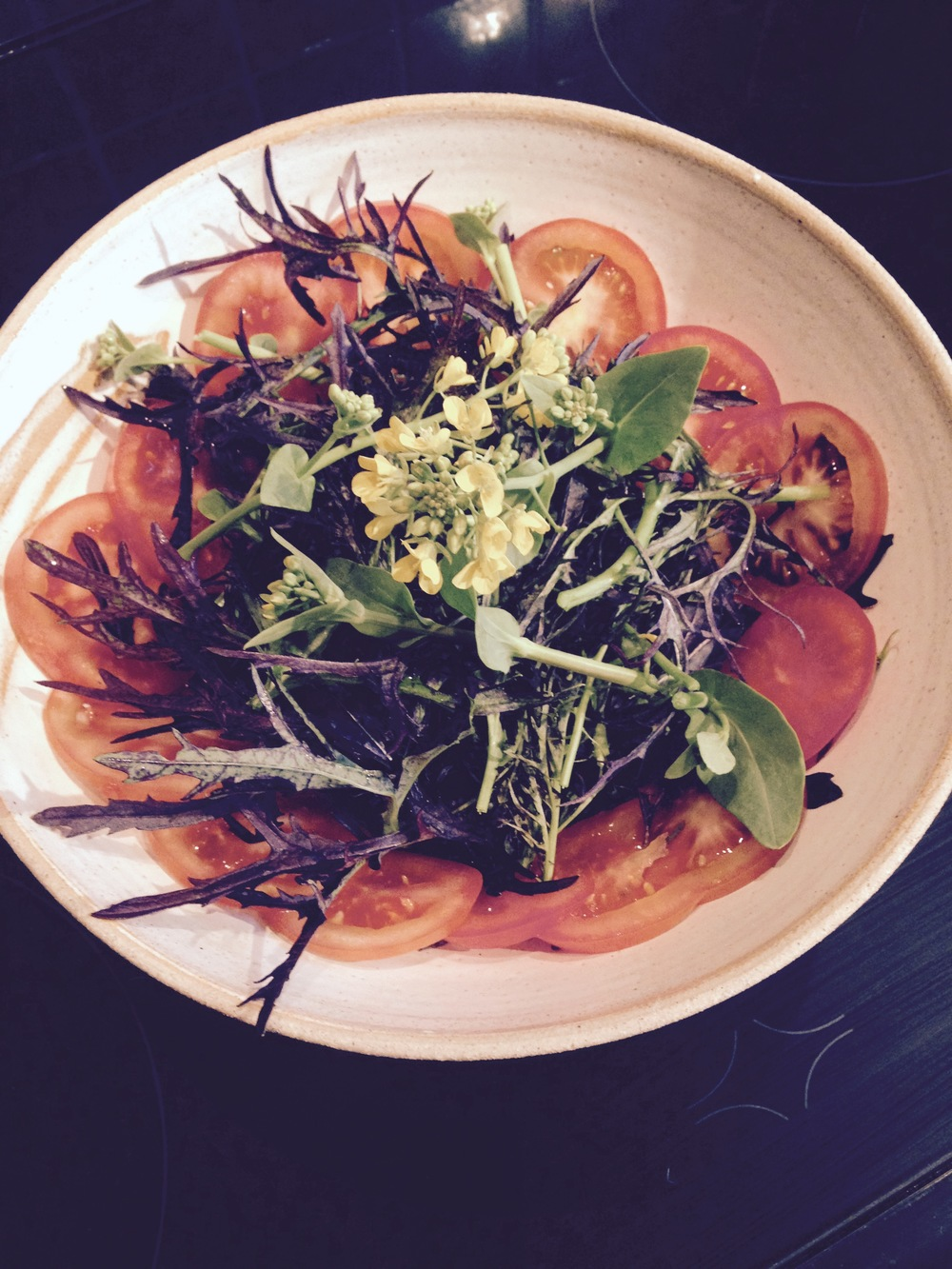 Tomato salad with red mizuna, flowering pak choi and sorrel leaves