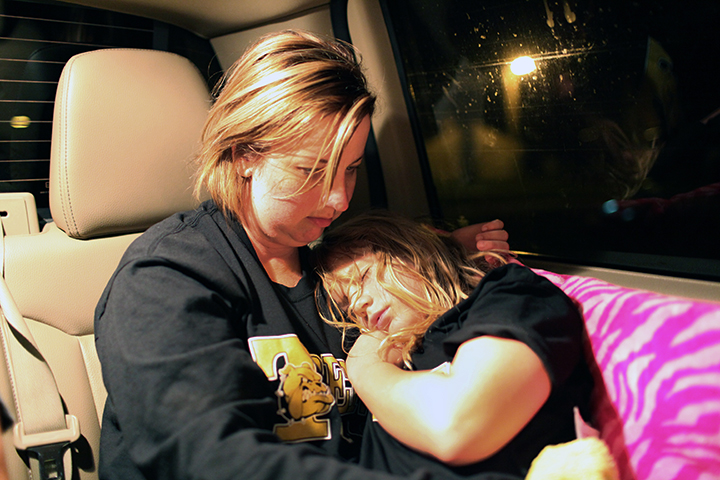 Rosetta holds a sleeping Serenity in the car ride home from her son's football game, two hours away from Trenton. Late nights are particularly difficult for Rosetta because her mornings start at 5 am.