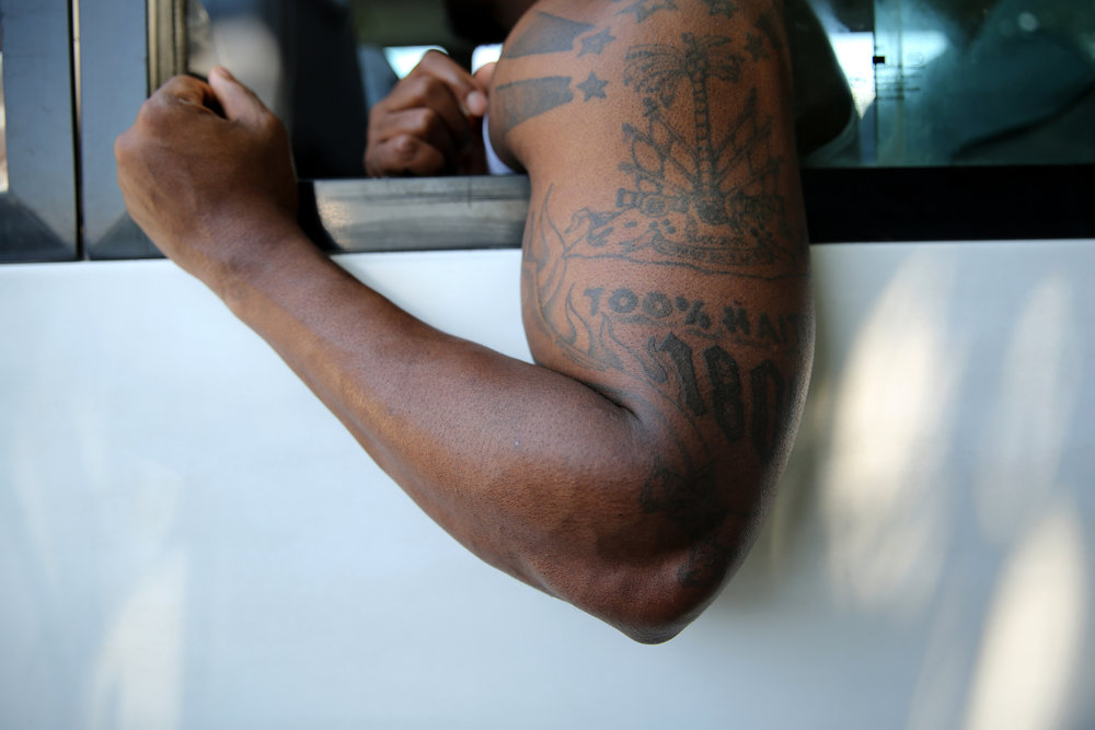 "Stevens Arnoux on a bus of Haitian-American deportees arriving at the Toussaint Louverture International Airport in Port-au-Prince in March 2014. He displays his tattoo, which says ""100% Haitian 1804."""