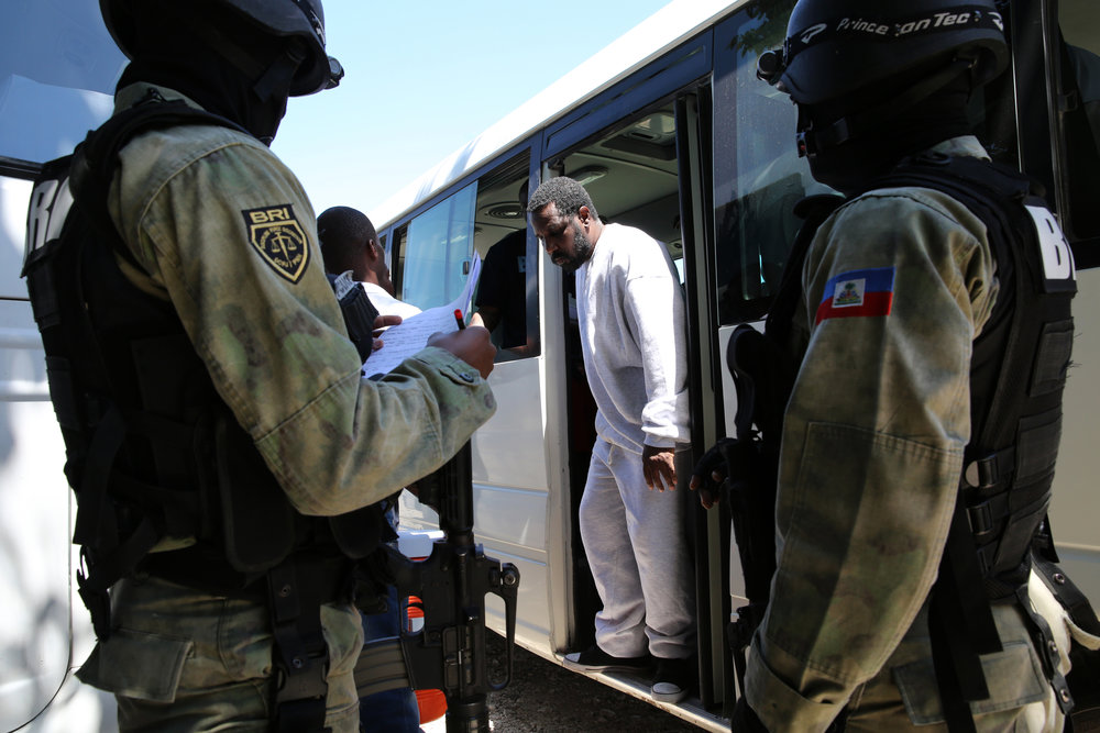 A Haitian-American deportee is escorted off to Haitian officials to gather his belongings and be issued an identification card.