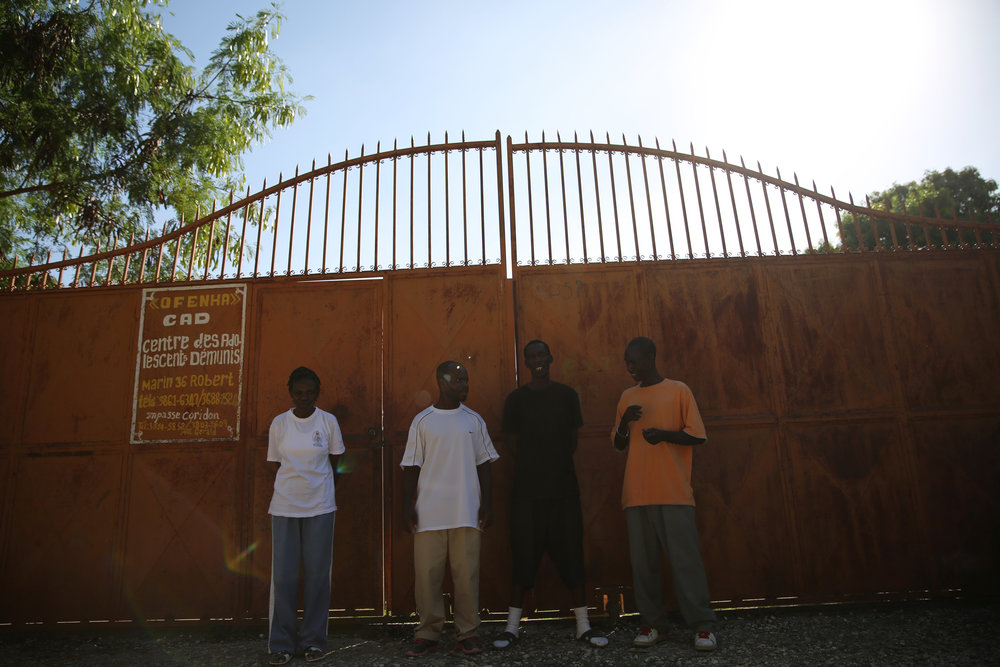 Haitian-American deportees gather outside of the accommodation center after being kicked out over an issue with the television remote control. They plan on staying with Gerard Faublas (orange shirt), a deportee who was able to receive financial assistance for an apartment before organizations that helped deportees lost funding.