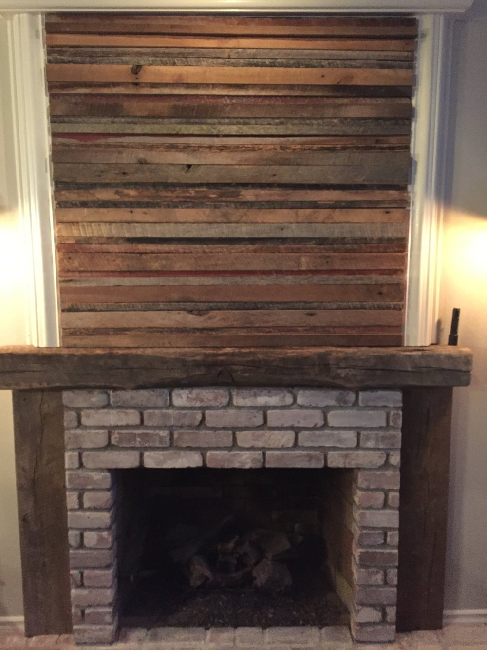 This wonderful and unique fireplace is a customer build using reclaimed wood paneling and a reclaimed beam mantel.