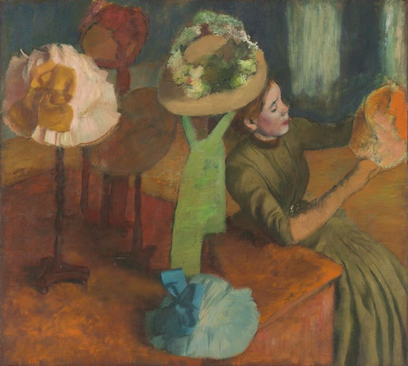 The Millinery Shop, by Edgar Degas.  Along with his painting, the Milliners, this painting illustrates a millinery shop, this time showing a customer examining a hat.