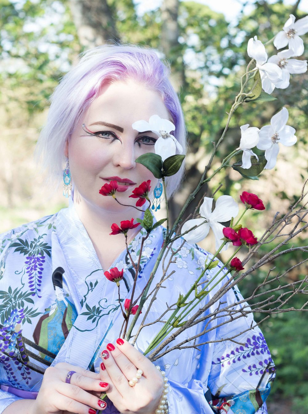 girl with lavender hair in blue kimono holding white and red flowers