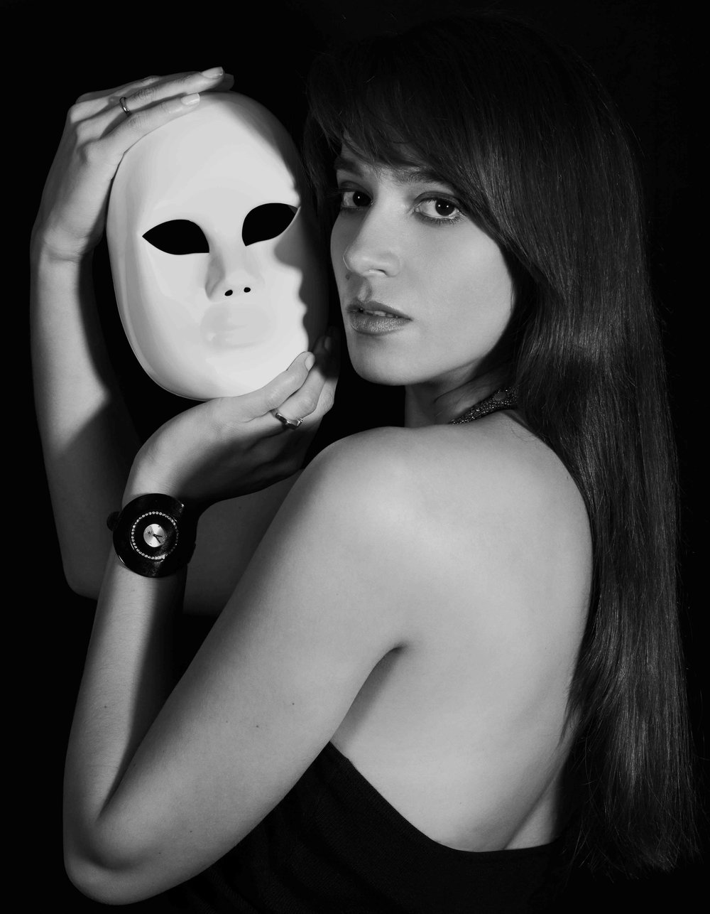 black and white portrait of a woman holding a mask