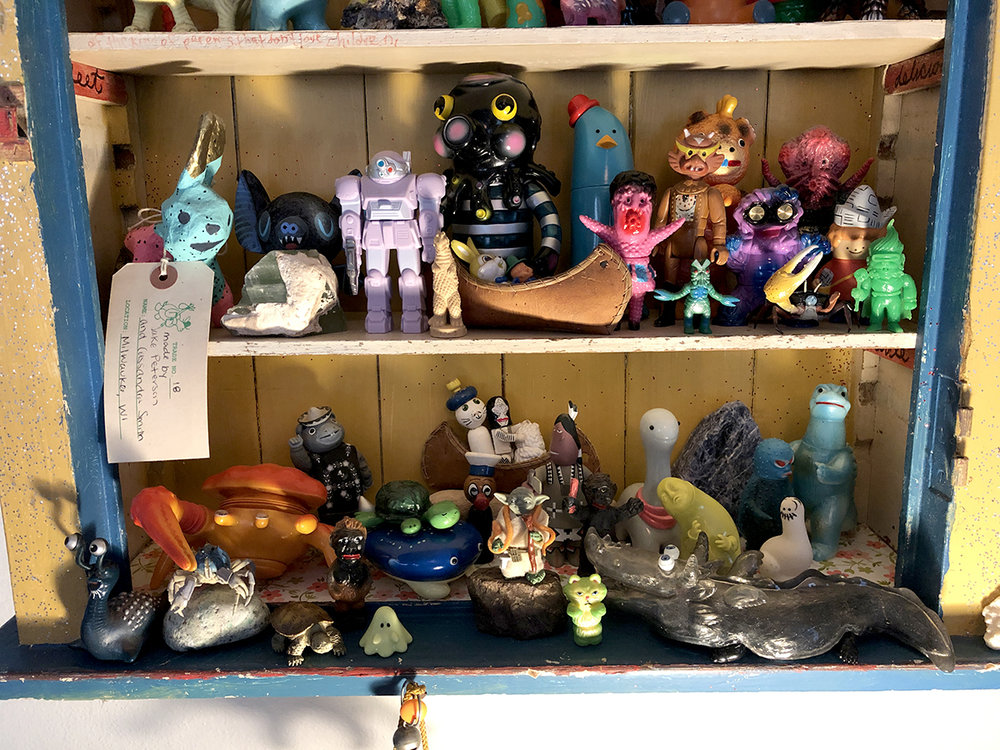 Upper shelf L-R- Crazy beast I got from Souther and Monica's traveling trade tortoise event at Grass Hut. Cool rock. Amanda Bat. Gargamel Votom. Neronga Ultra villian or is it Bemler? Globby. Bunny and a Moonshiner in a leather canoe. Chima banana. Anraku critter. Tiny Baltan. Star Raider. Buta Booska Lady. Little Gargamel smashface hedo. crabby gashapon. Anraku buddy. Little Bubi guy. Keshi New Terry.  Bottom Row L-R- Namegon. Gashapon crabby on a rock. Sofubi not so soft anymore crabby with accordian plunger on top. Gashapon snapping turtle. Booska in a poncho. Buta cave dude. Chima Manta with a walnut shell turtle my mom made on top.Another leather canoe with little wooden toys, ultra Dada, baby treeson inside. James Jarvis native american. Yoda. Grumble kitty. Buta cave guy. Chima Dino. Shimomoku critter. T9G double dragon/sally. Kure Kure Takora guy. Shmoo. and Zilla made maybe by Toygraph.
