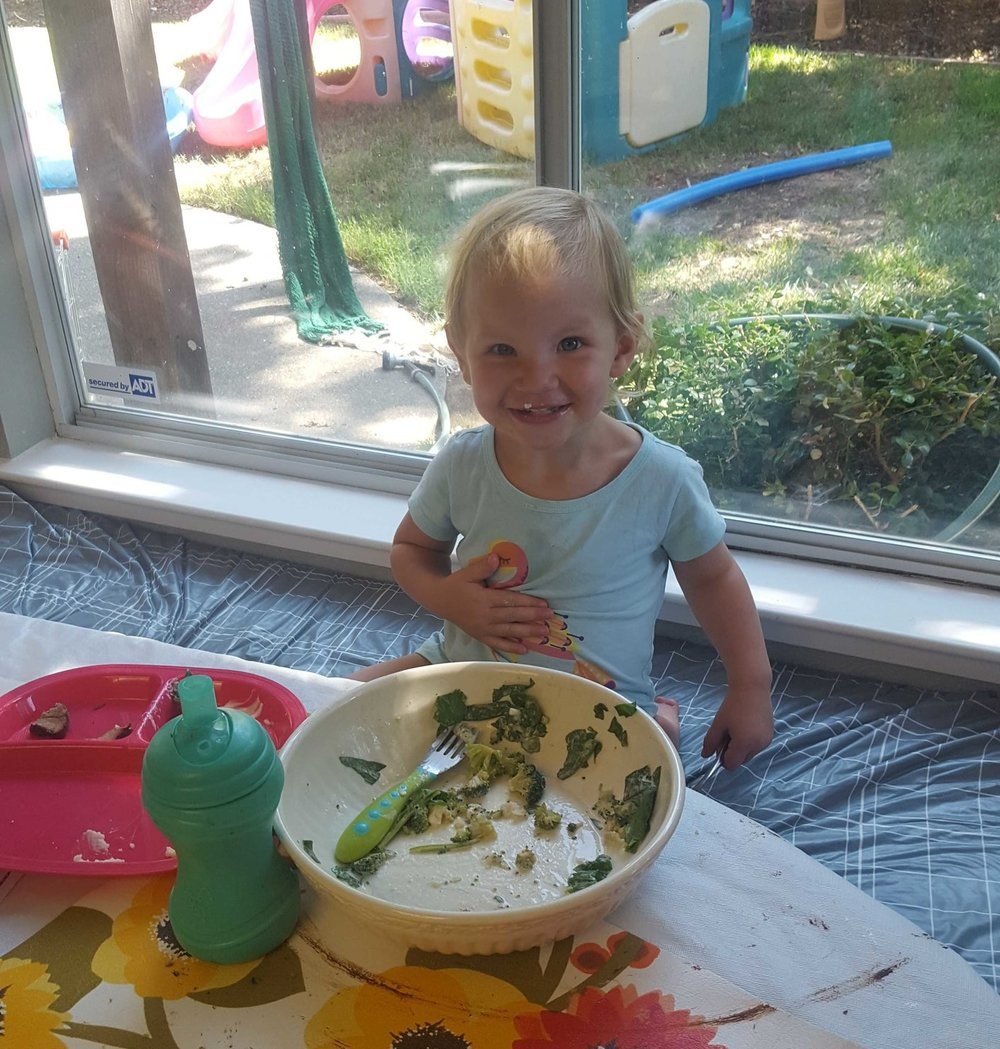 Madeleine enjoying her lunch of spinach and broccoli.